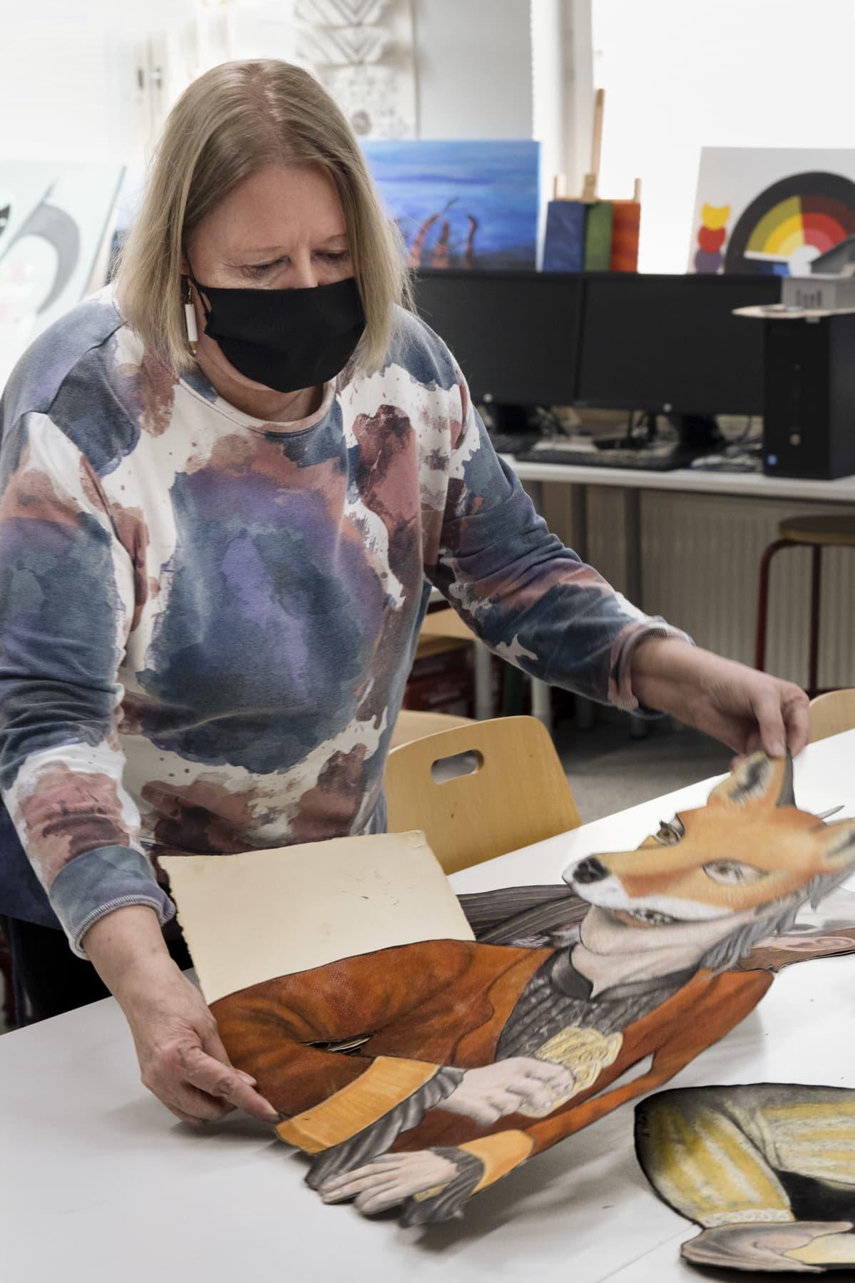 Heidi Möller-Virtanen näyttää lukiolaisen kuvamaataidon diplomityöhönsä piirtämiä hahmoja.