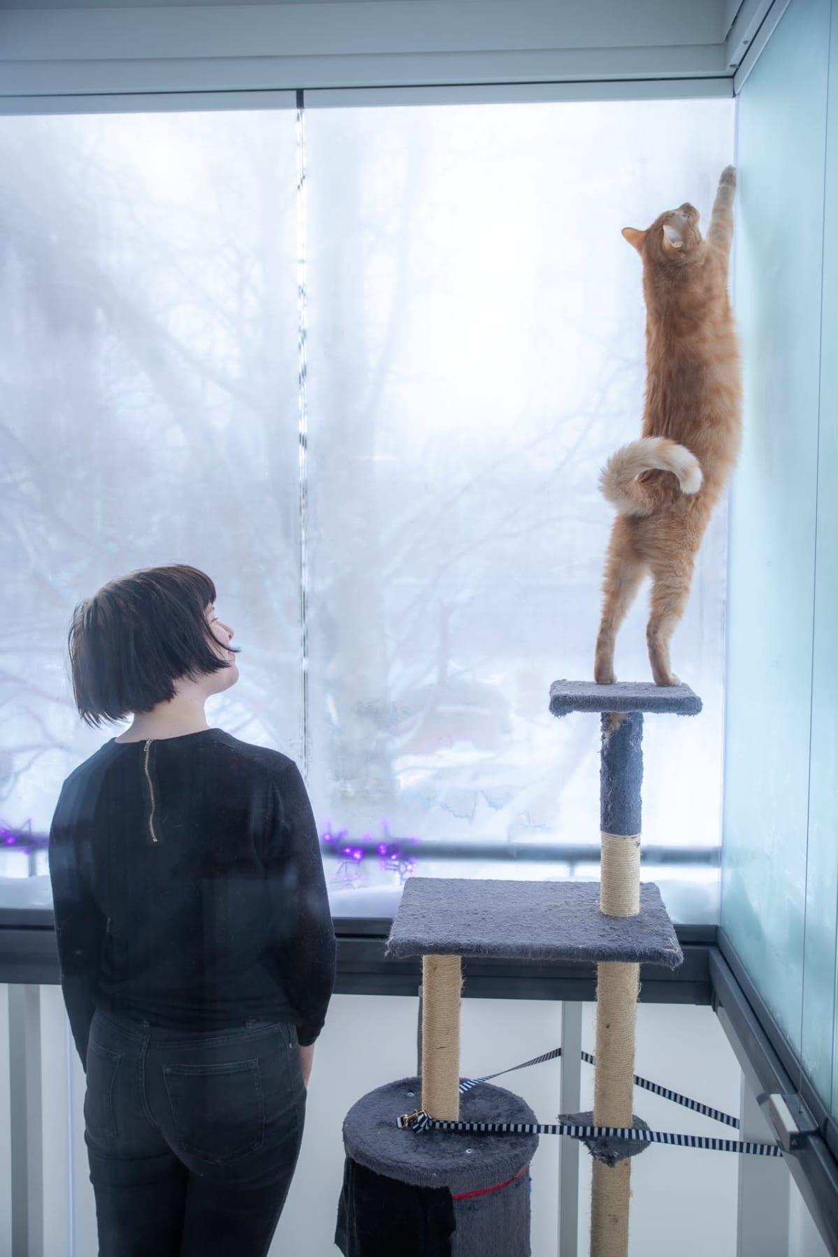 Isla Mäkinen seisoo parvekkeella kissansa kanssa