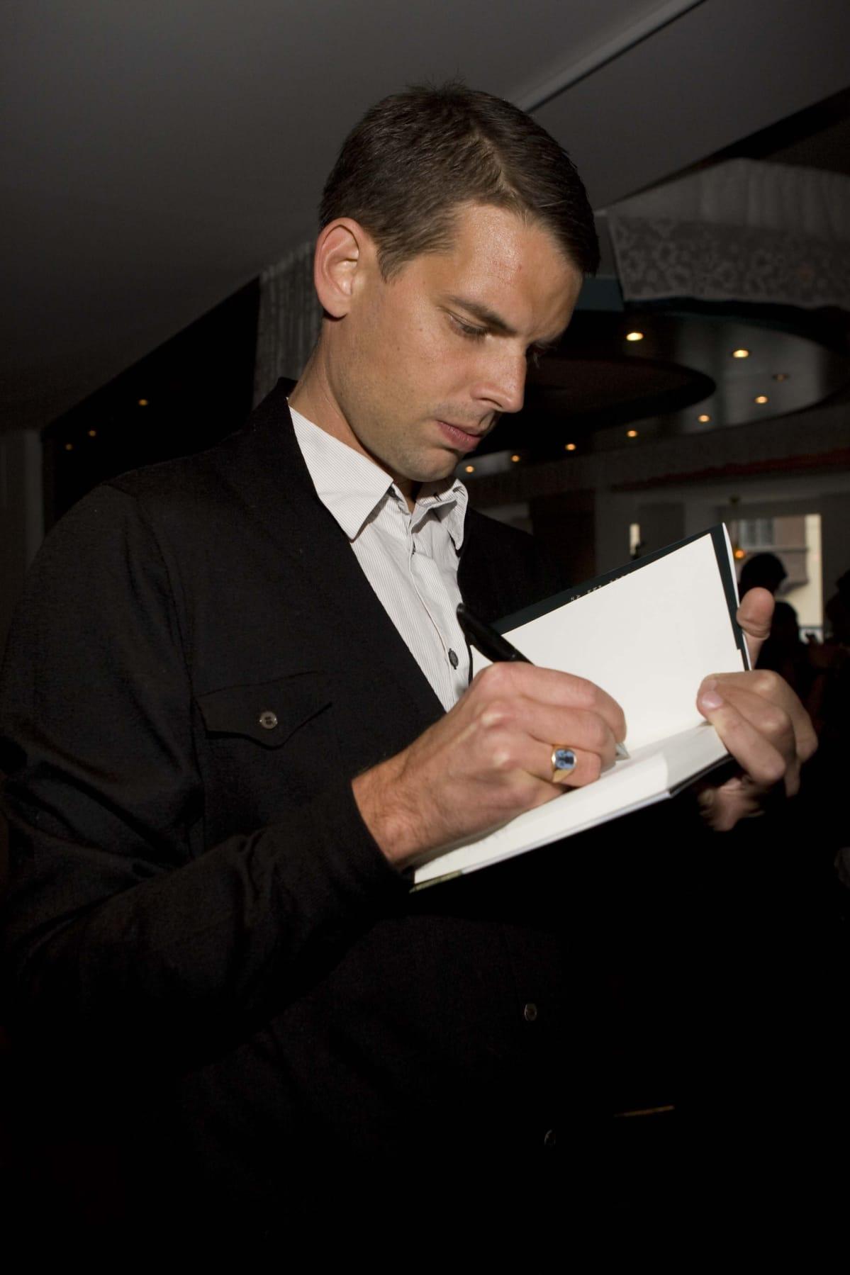 Alex Schulman antaa nimikirjoitusta.