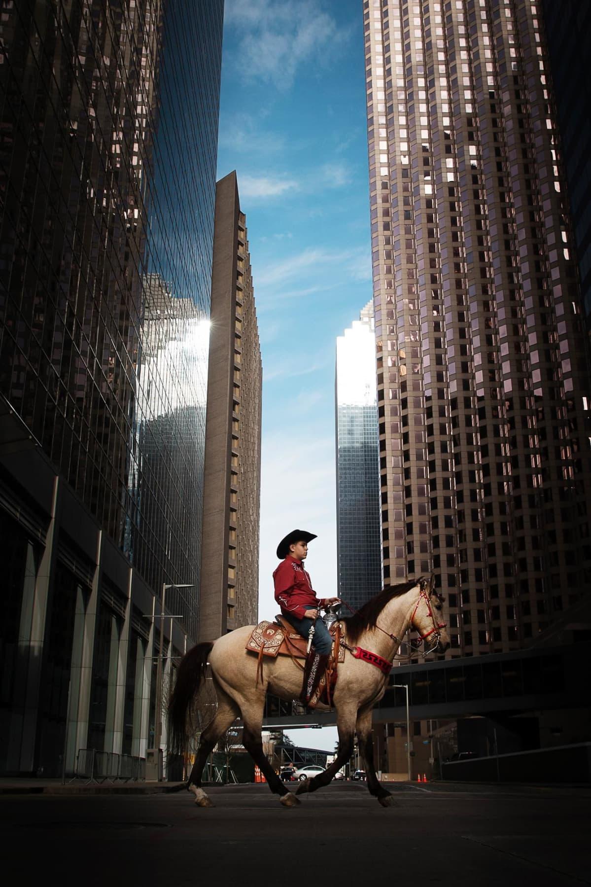 Cowboy ja hevonen kävelyllä kaupungissa.