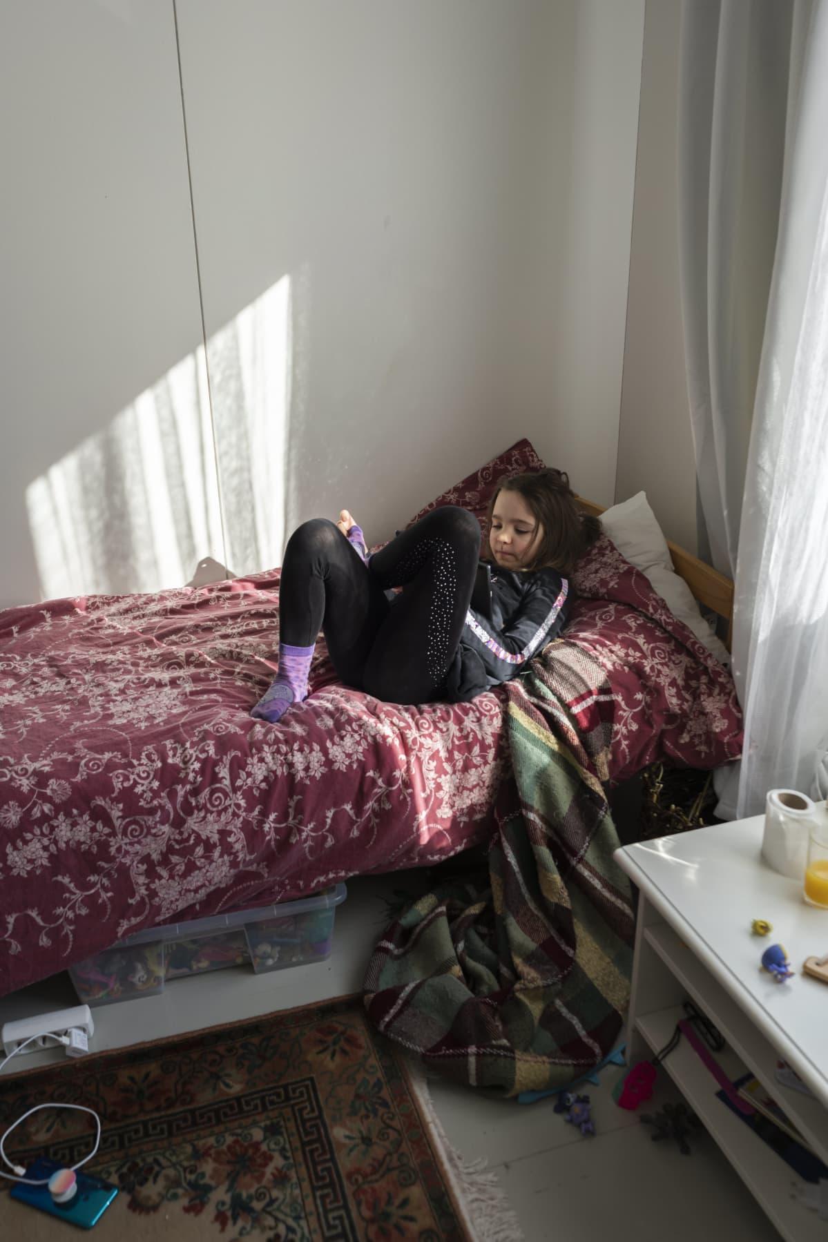 Tyttö makaa sängyllä ja käyttää taulutietokonetta. Aurinko paistaa ikkunasta huoneeseen.