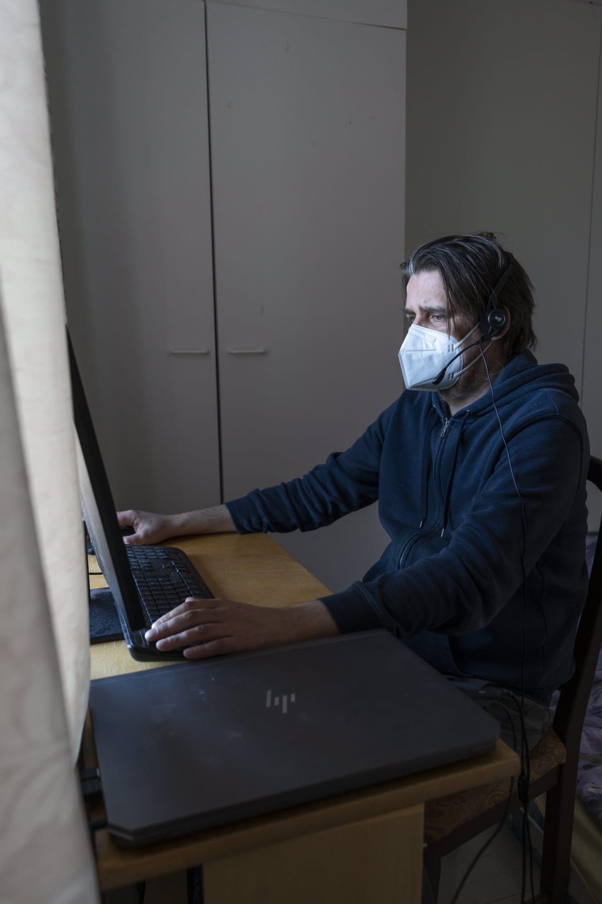 Mies istuu tietokoneen äärellä keskittyneen näköisenä. Hänellä on päässään kuulokemikrofoni sekä suu- ja nenäsuojain.