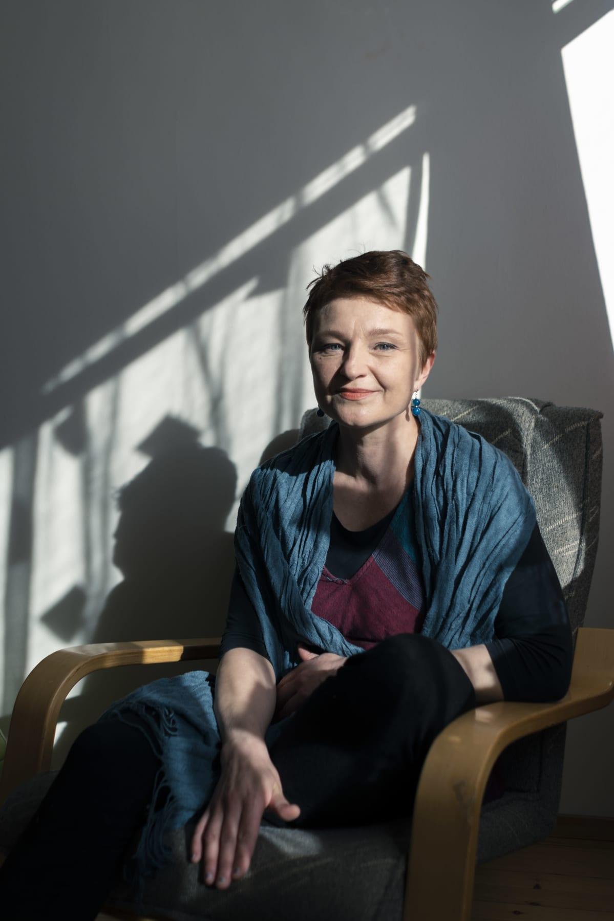 Nainen istuu tuolilla ja katsoo kameraan hieman hymyillen. Auringon valo valaisee naisen kasvot ja piirtää tervän varjon seinään.