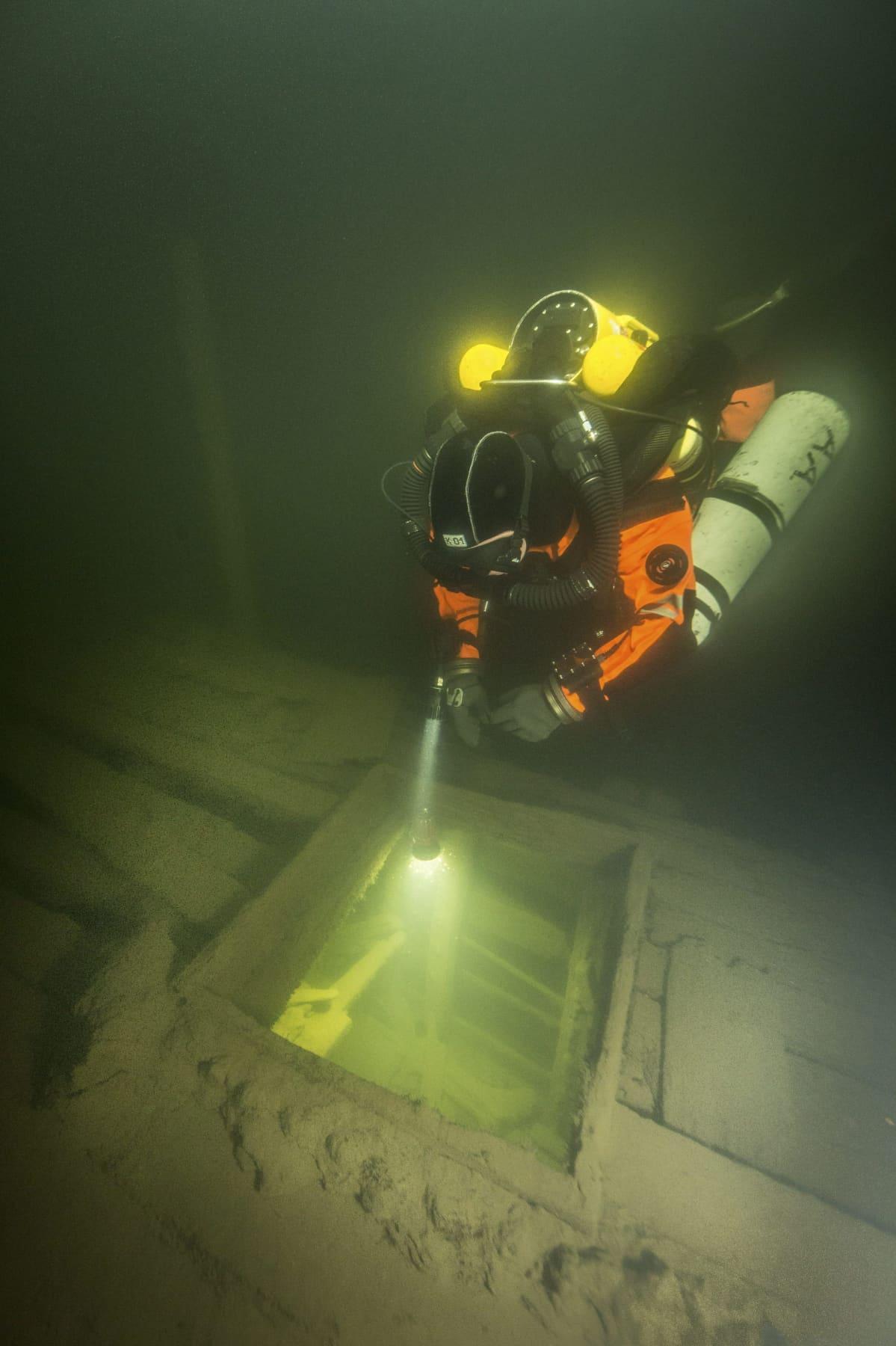 Sukeltaja tutkii Sipoon vesiltä löydetyn lähes täydellisesti säilyneen siipiratashinaajan hylyn keularuuman aukkoa.