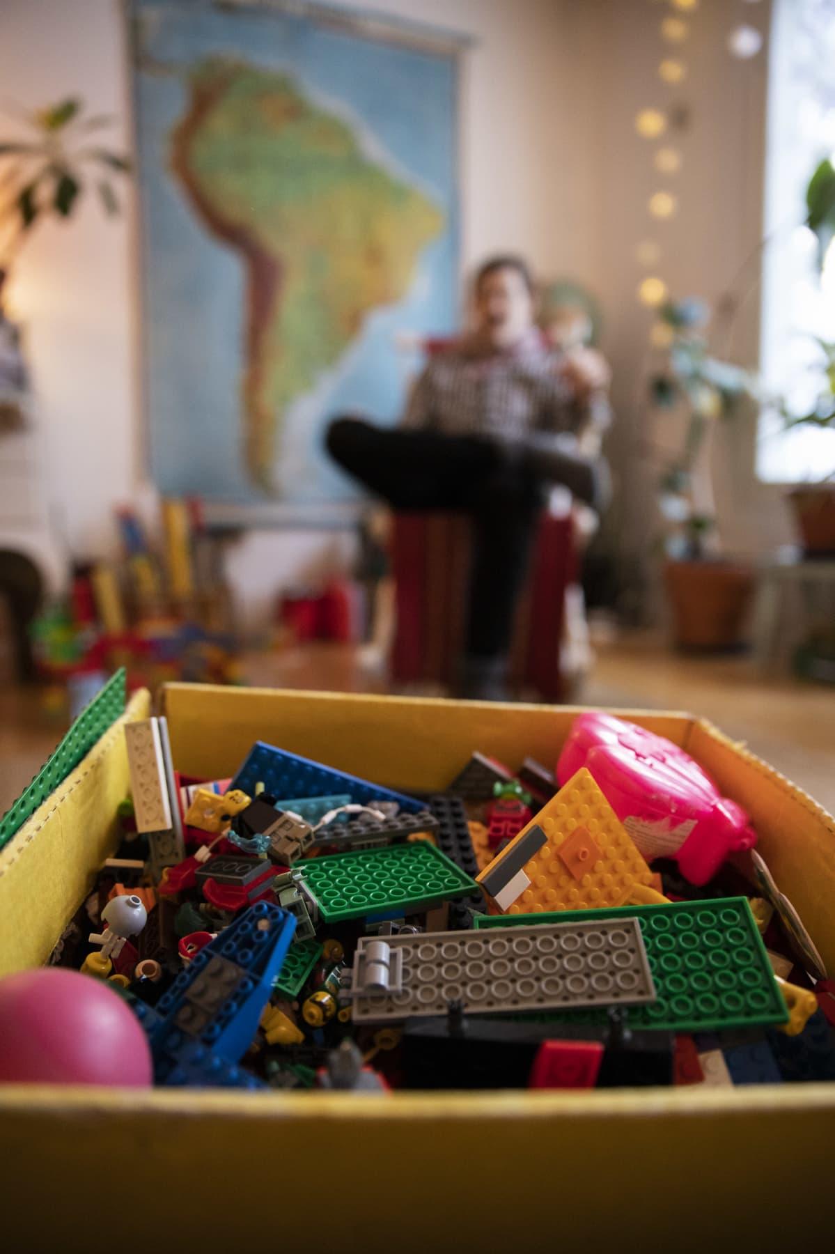 Legolaatikko lattialla, Joonatan Tola istuu taustalla kiikkutuolissa