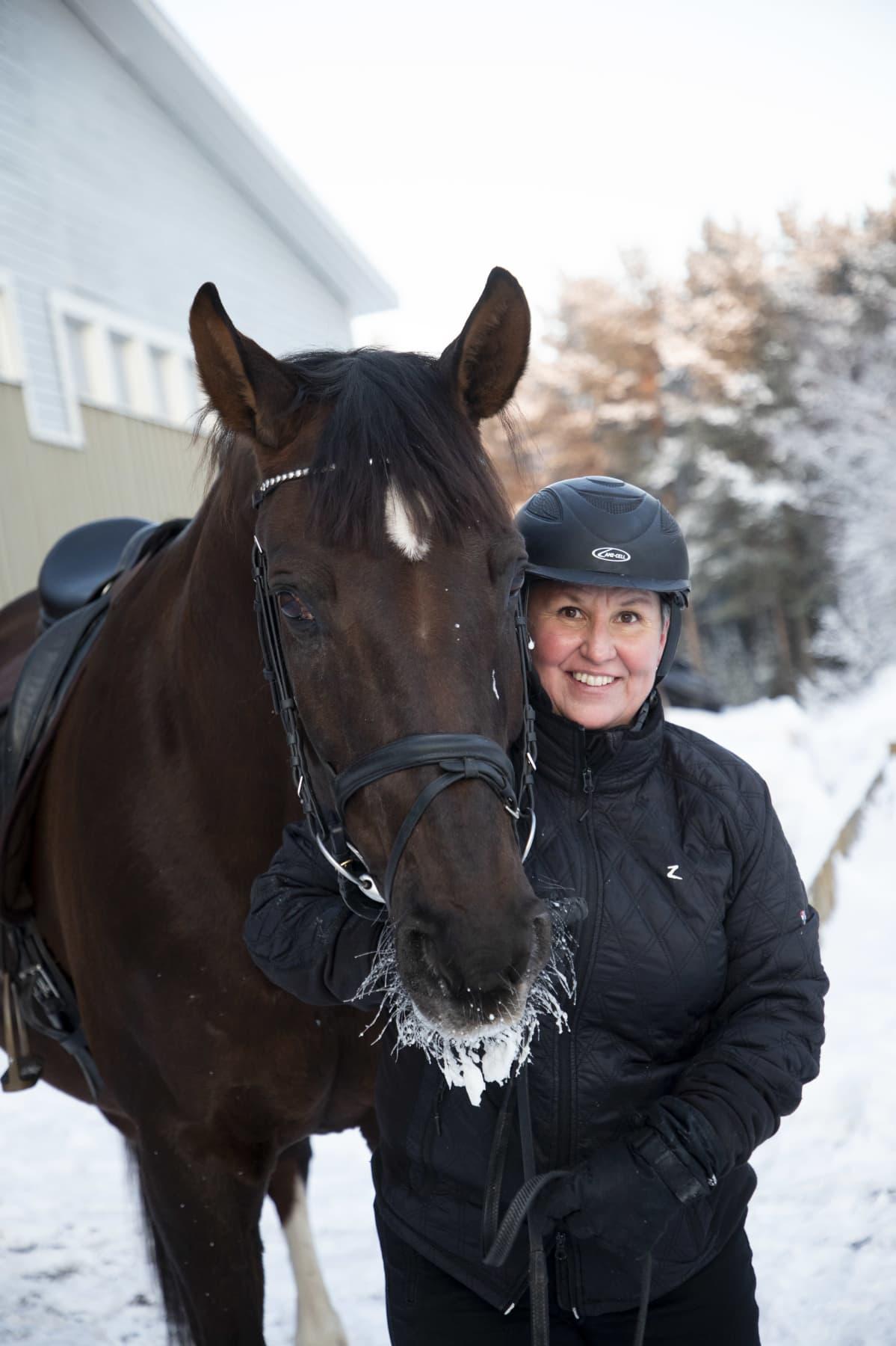 Marjukka Manninen seisoo hevosen vieressä.
