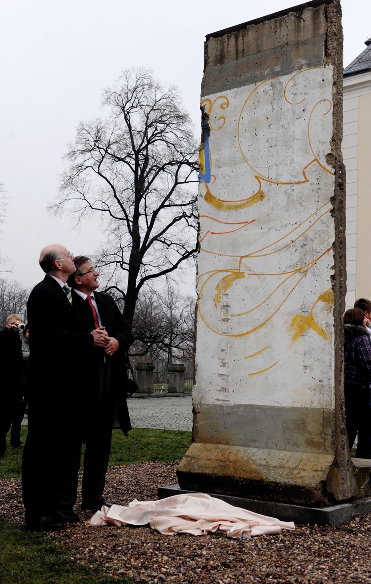 Yksi lohko berliinin muuria syksyisessä puistossa kahden miehen edessä.