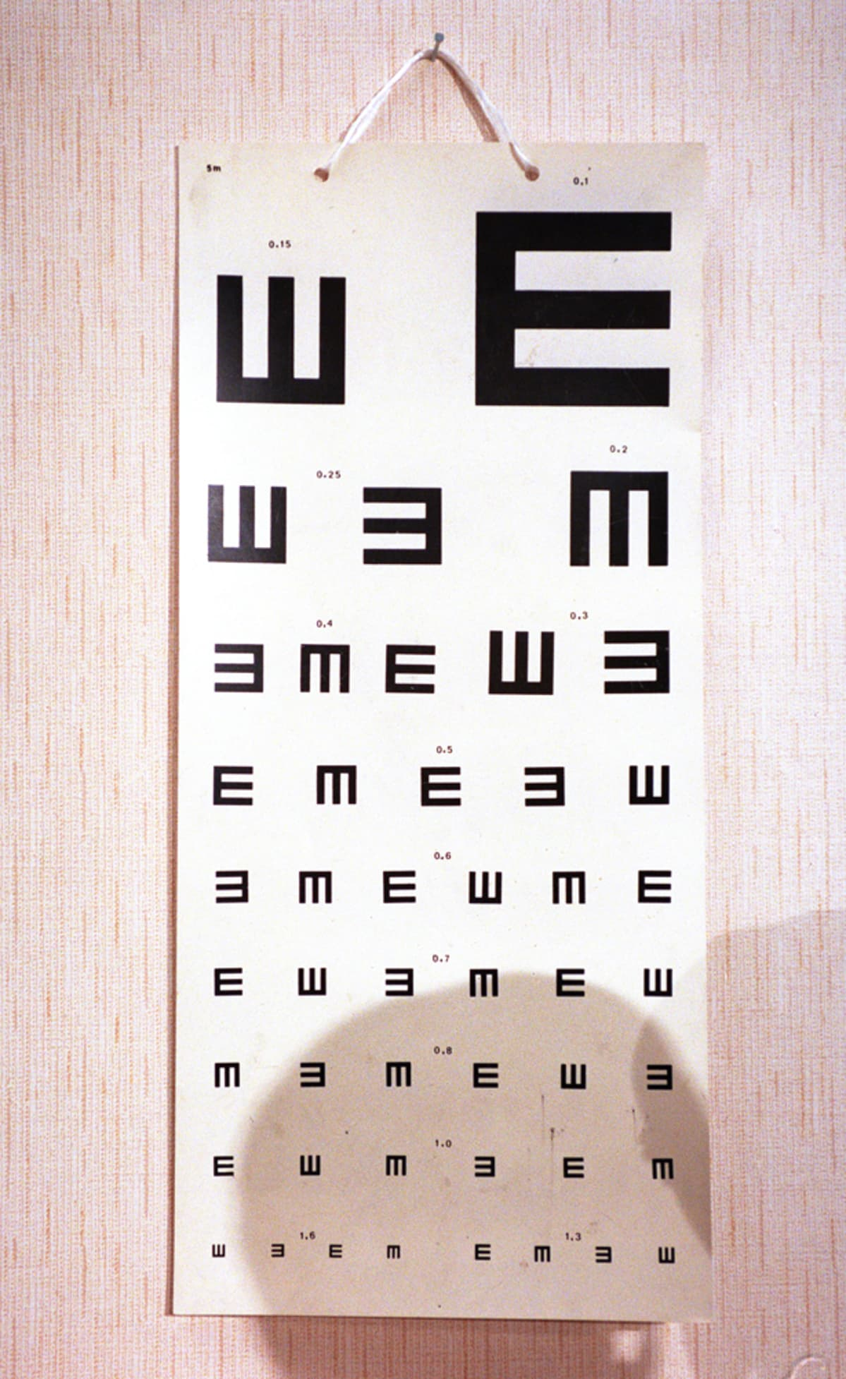 Näön tarkastamisessa käytetty taulu, jossa on eri suuntiin olevia kirjaimia.