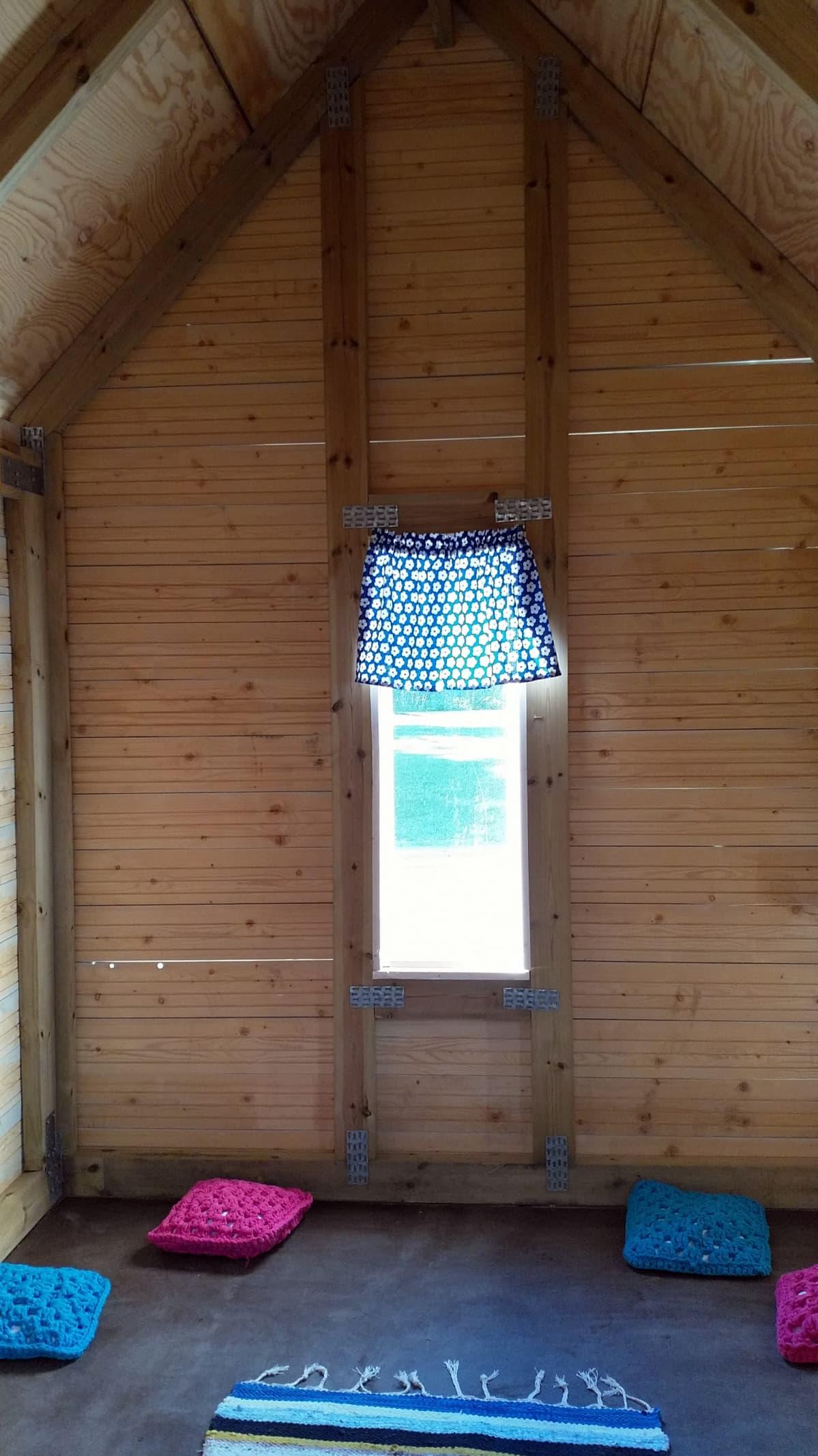 Kuvassa leikkimökki sisältä. Lattialla on neljä virkattua tyynyä ja räsymatto. Ikkunassa on verho.