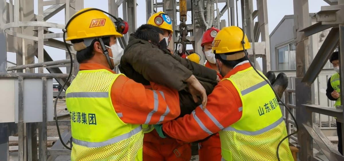 Neljä pelastustyöntekijää kantaa maan alta pelastettua kaivostyöläistä. Miehillä on oranssit haalarit, kirkkaankeltaiset huomioliivit, keltaiset kypärät ja kasvomaskit. Ympärillä näkyy puisia rakenteita.