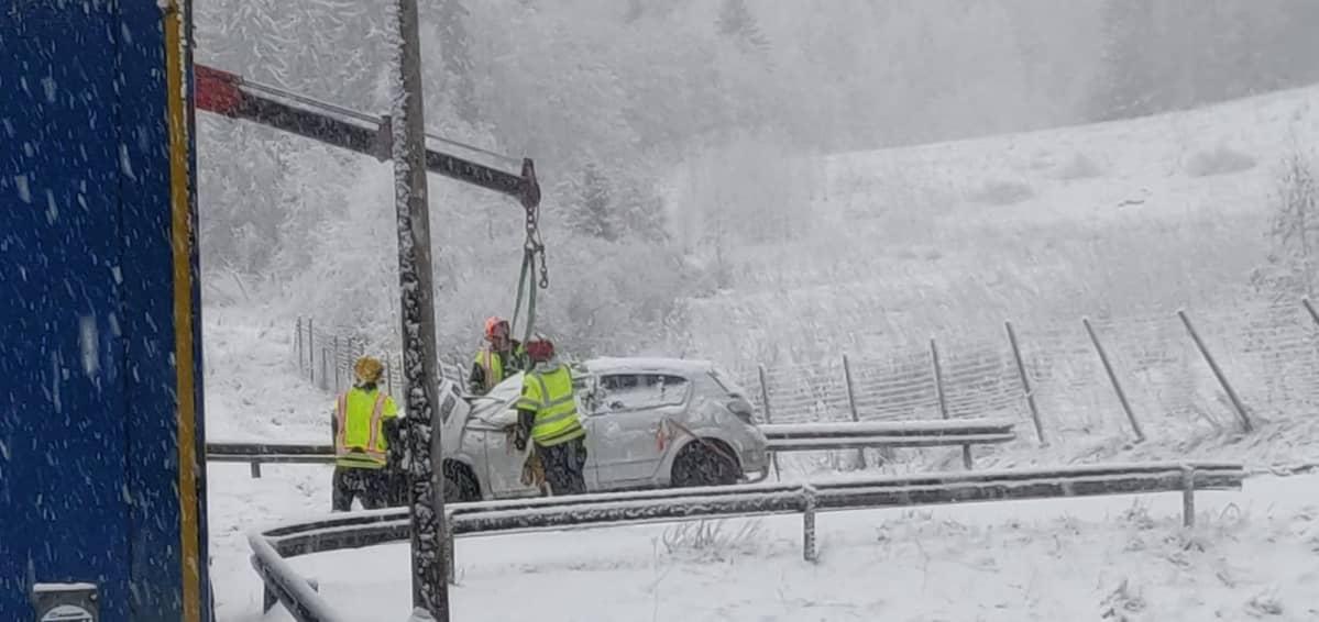 Auton nostetaan ojasta lumisella onnettomuuspaikalla.