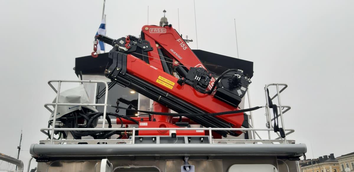 Punainen suuri nosturi laivan kannella.