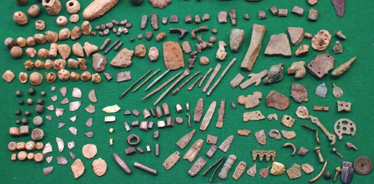 Satoja pelinappuloita, korujen kappaleita ja muita pienlöytöjä pöydälle aseteltuina.
