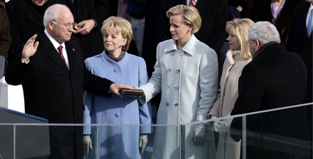 Dick Cheney vannoo virkavalaa toinen käsi kohotettuna ja toinen Raamatun päällä. Liz Cheney katsoo isäänsä.