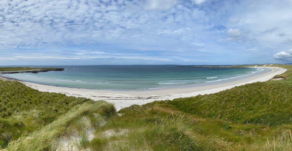 Maisemakuva Ulko-Hebrideiltä. Kuvassa merenranta, ulappa ja pilviä taivaalla.