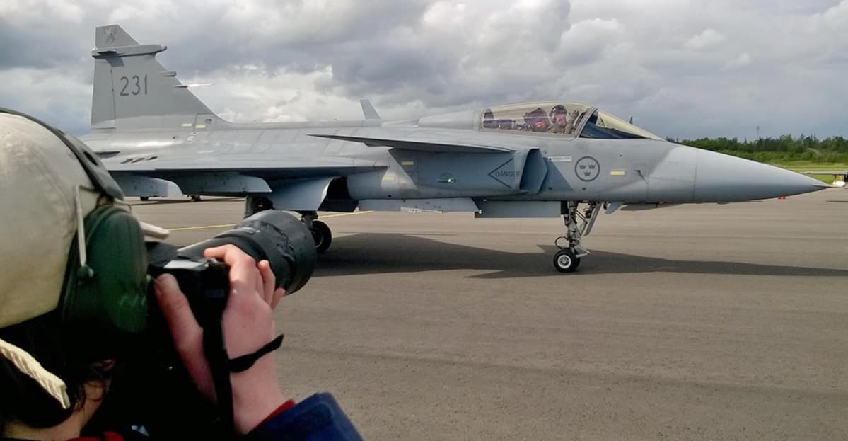 mies kuvaa kentällä olevaa lentokonetta