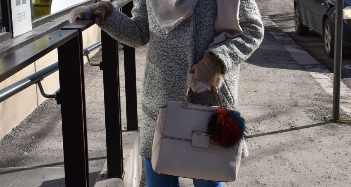 nainen esittelee vaatteitaan kadulla