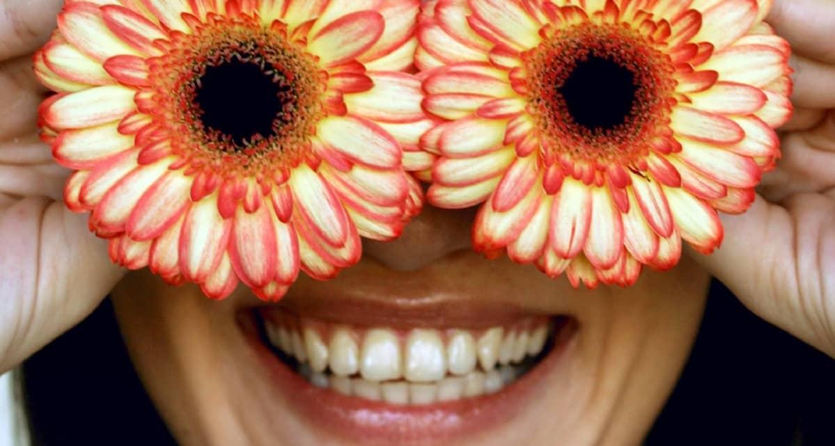 Nainen pitää kahta gerberankukkaa silmiensä edessä ja hymyilee leveästi.