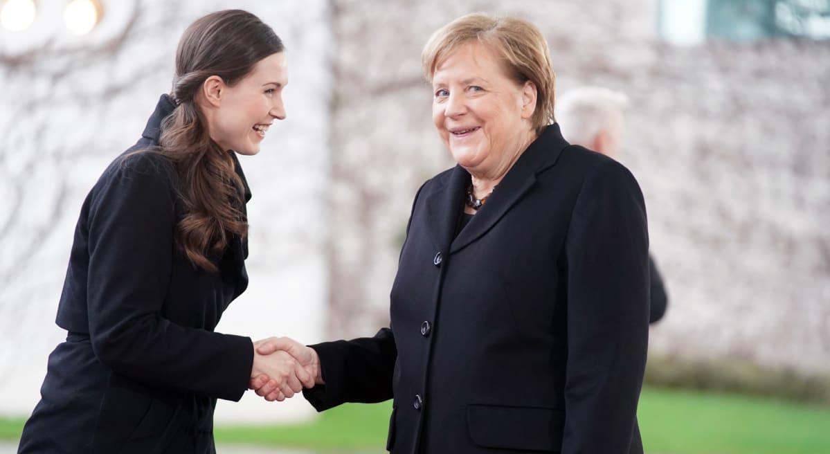 Sanna Marin ja Angela Merkel kättelevät hymyillen.