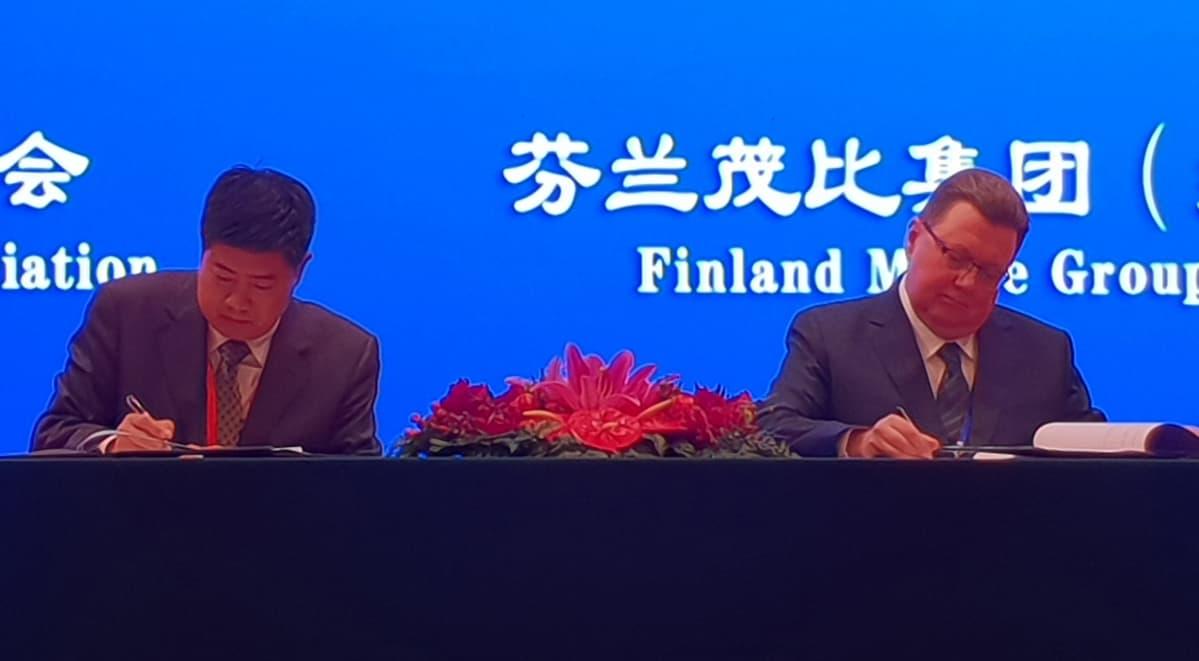 Mobie Groupin hallituksen puheenjohtaja Kari Vatanen allekirjoittaa koulutusvientisopimuksen pääsihteeri Yang Zijianin kanssa Kiinan  kansojen hallissa pidetyssä konferenssissa.
