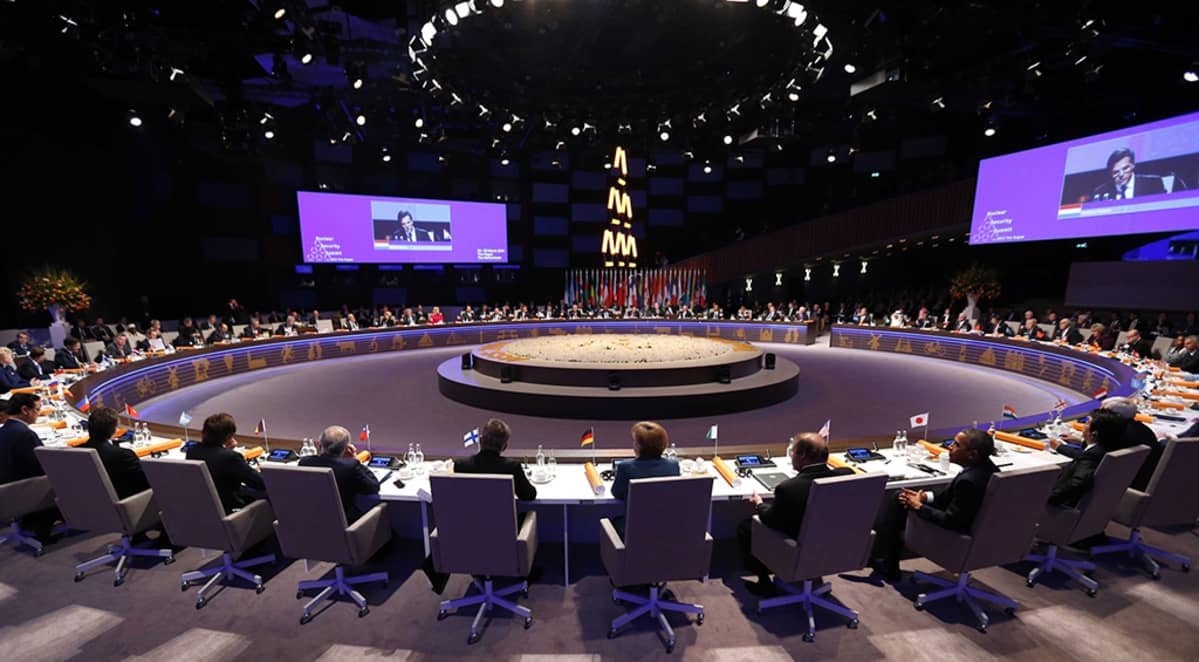 kokoontujat istuvat suureen ympyrään asetetuissa pöydissä