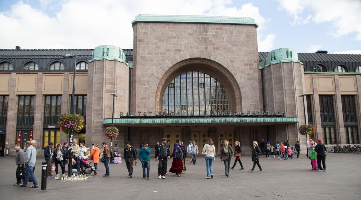 Ihmiset sytyttivät kynttilöitä ja toivat kukkia Helsingin Asema-aukiolle.