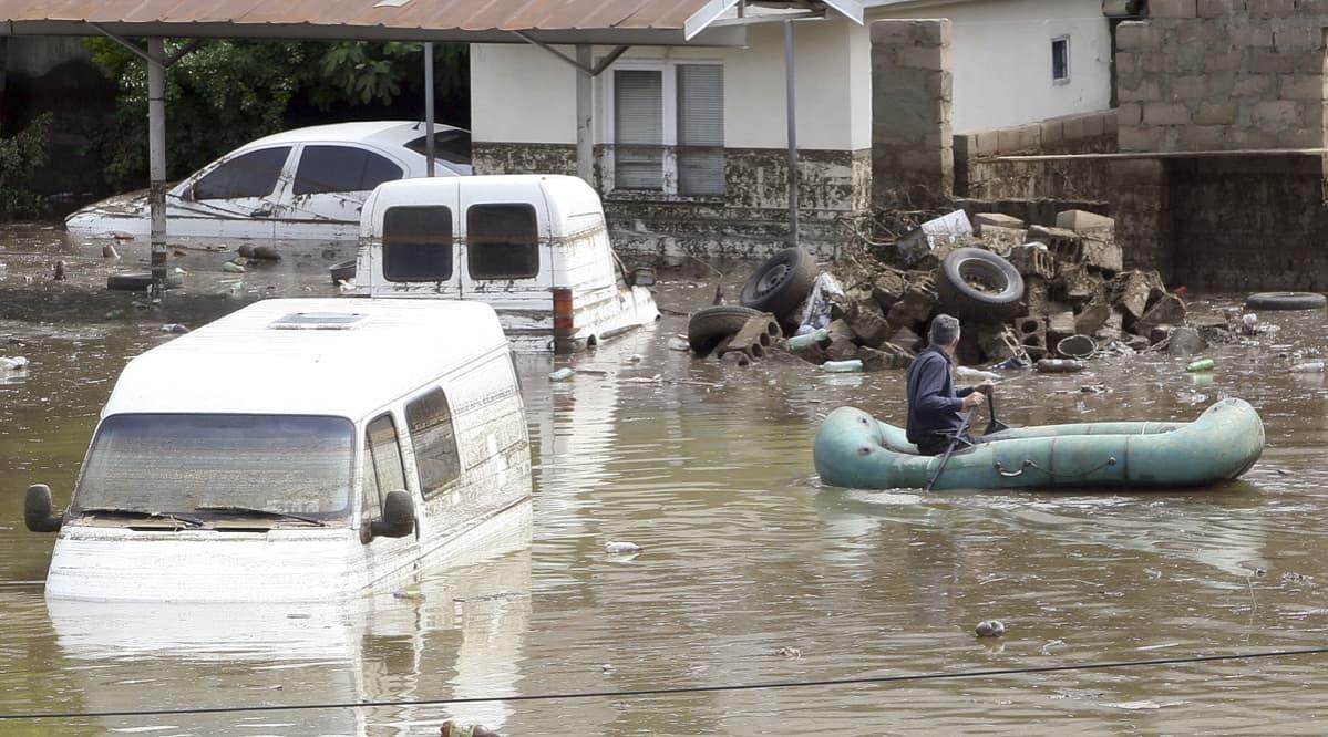 Mies soutaa kumiveneellä autojen seassa veden täyttämällä kadulla.