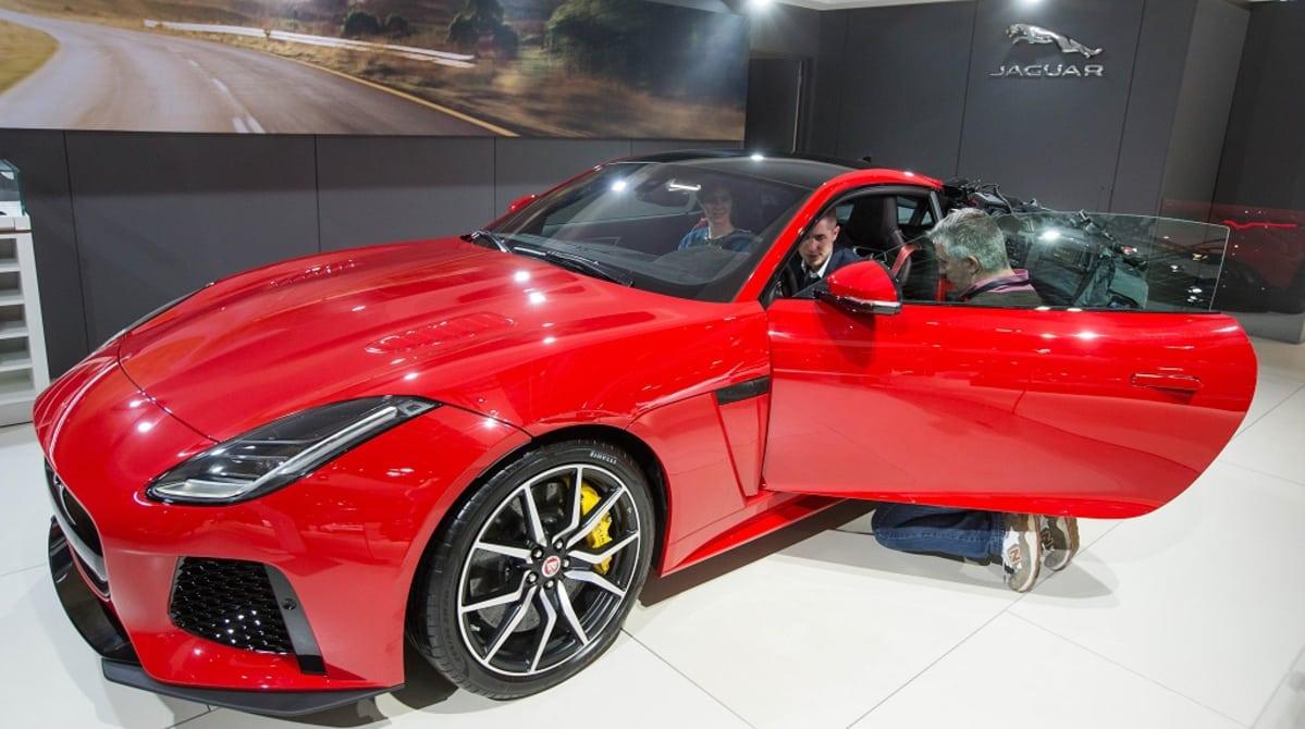 Punainen urheiluauto, jonka sisällä istuu mies ja nainen ja vieressä on mies polvillaan.