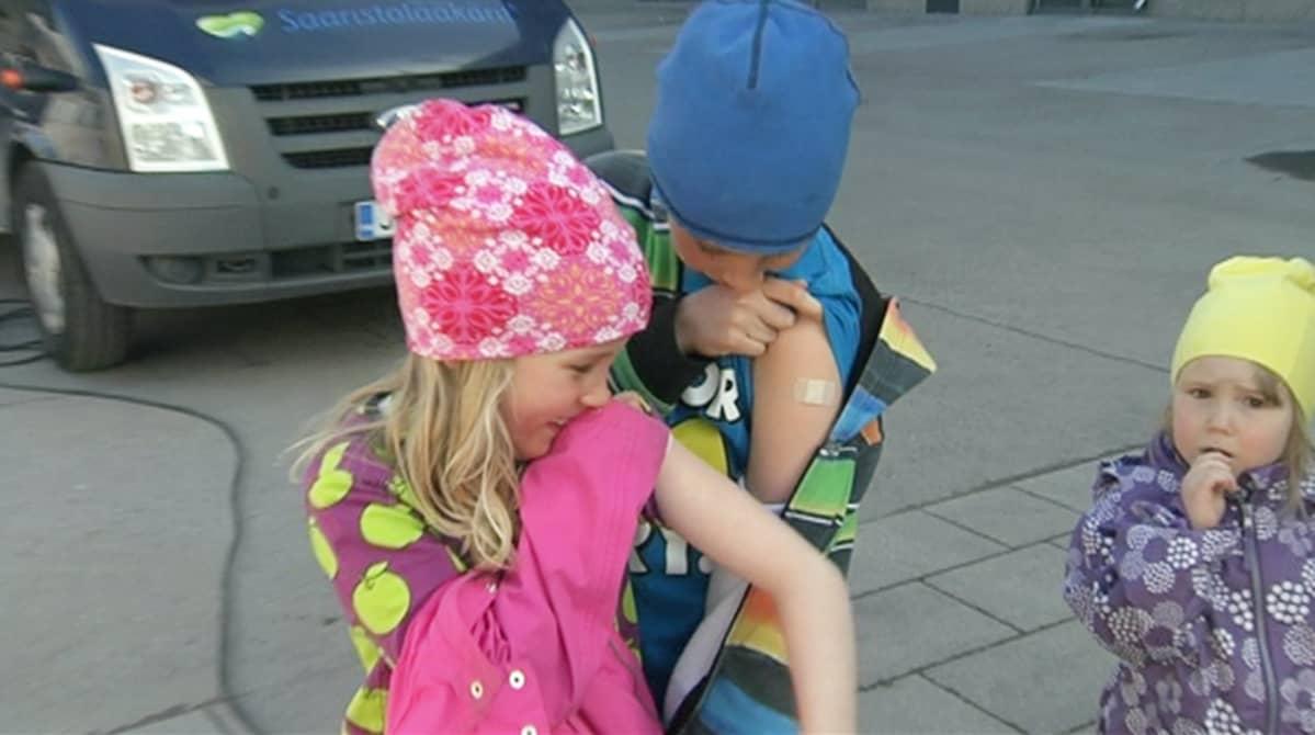 Lapset katsovat punkkirokotuksen jälkiä käsivarsissaan.