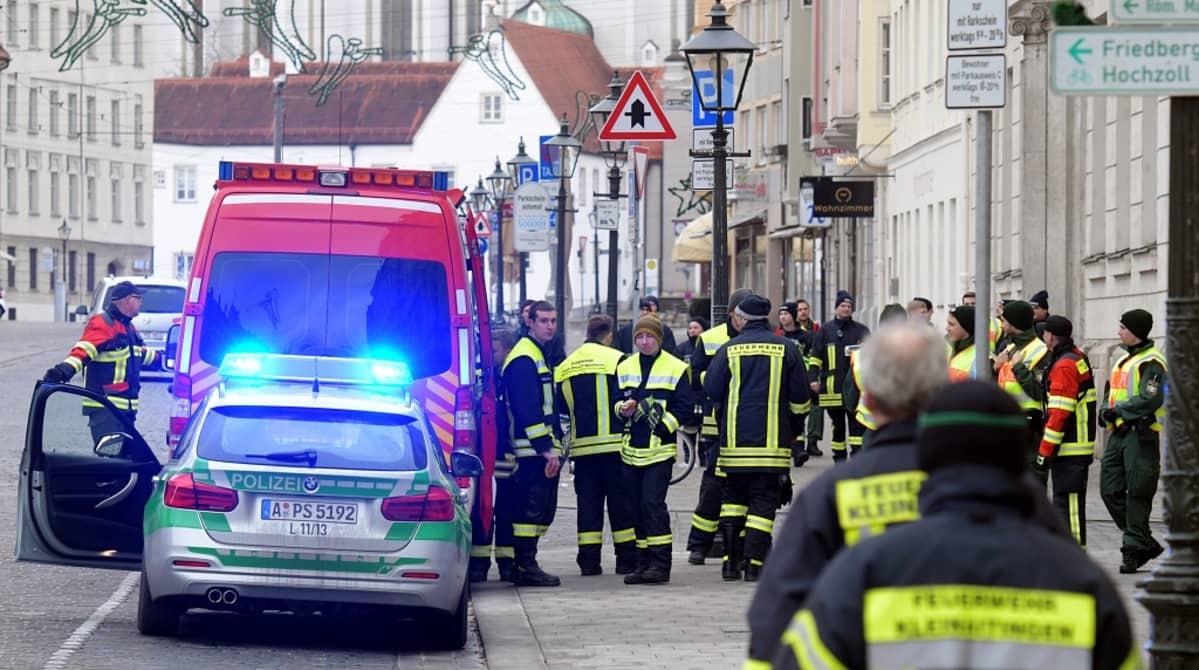 Poliisiauto, ambulanssi ja pelastustyöntekijöitä autiolla kadulla.