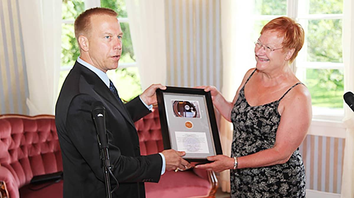 Astronautti Kopra luovuttaa Kalevala-mitalin presidentti Haloselle Kultarannan Munkkimäessä heinäkuusa 2010.