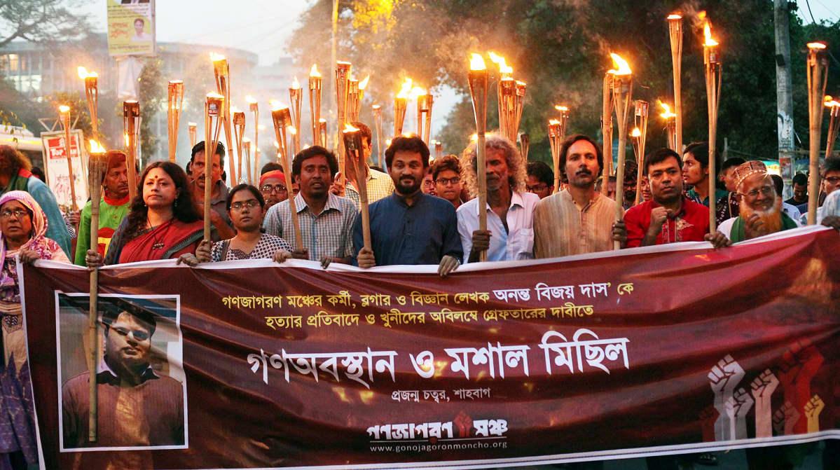 Mielenosoittajiat pitelevät palavia soihtuja ja muistobanderollia.