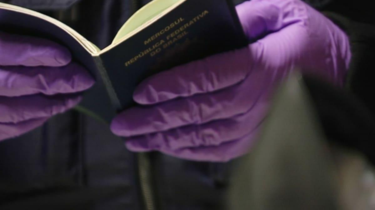EU:n ulkopuolisen valtion passi poliisin kädessä.