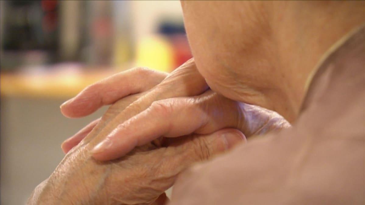 Lähikuvassa iäkkään naisen sormet ristissä.