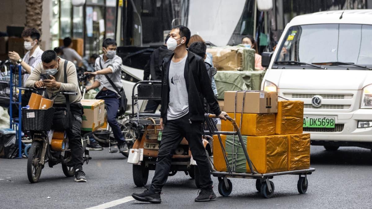 mies vetää kärryä jossa kännykkälaatikoita Guangzhoussa