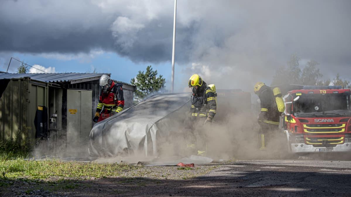 Palomiehet sammuttavat sammutuspeitteella autopaloa.