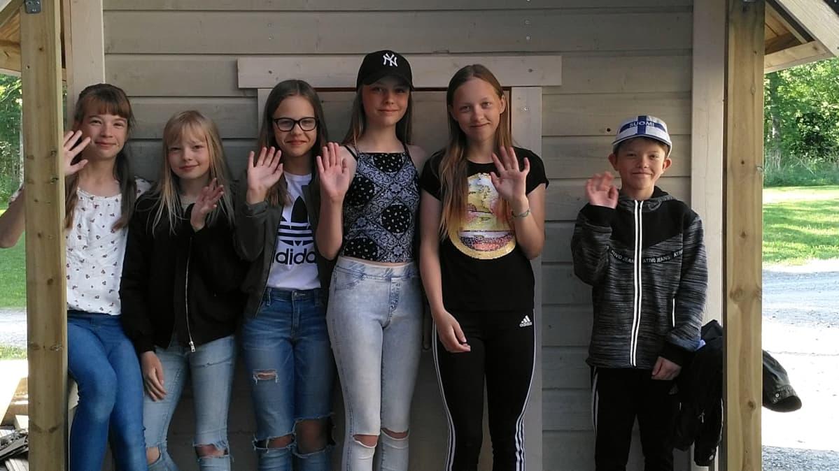 Kuvassa kuusi oppilasta seisoo leikkimökin edessä ja vilkuttaa.