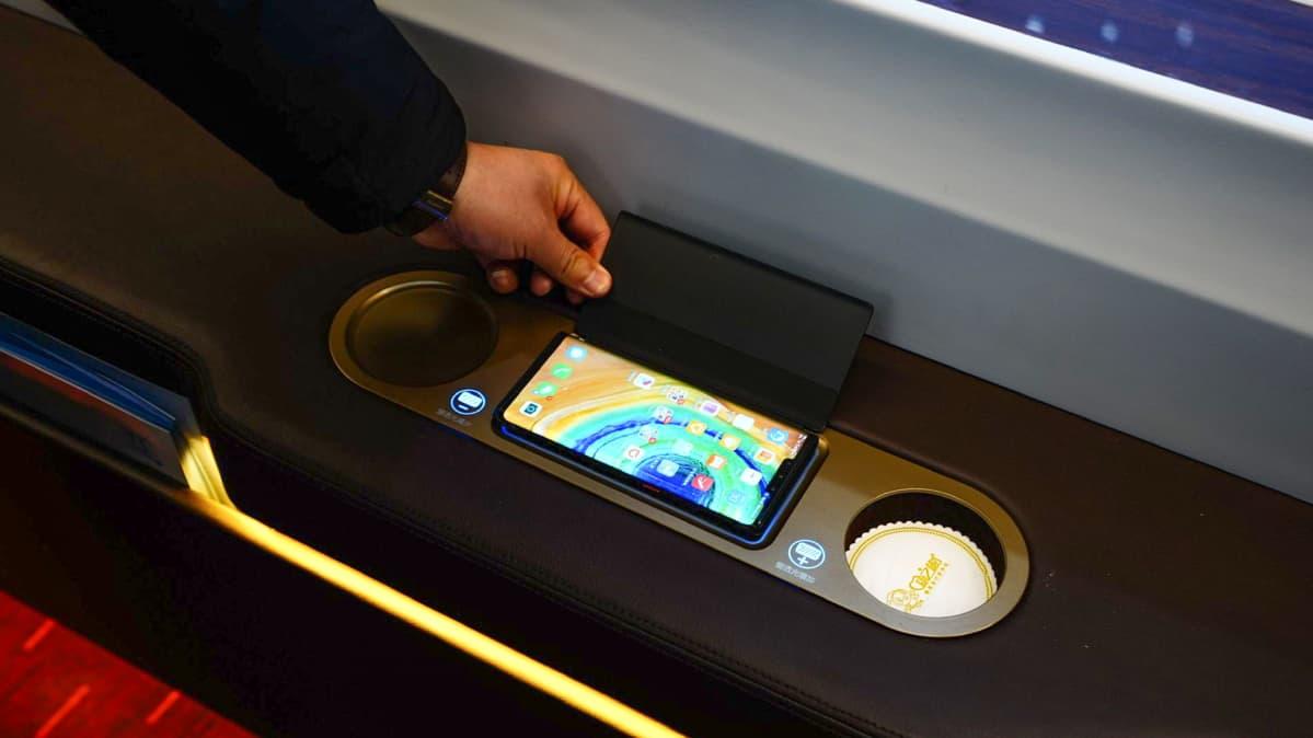 Älypuhelimen langaton lataus junavaunussa Kiinassa.