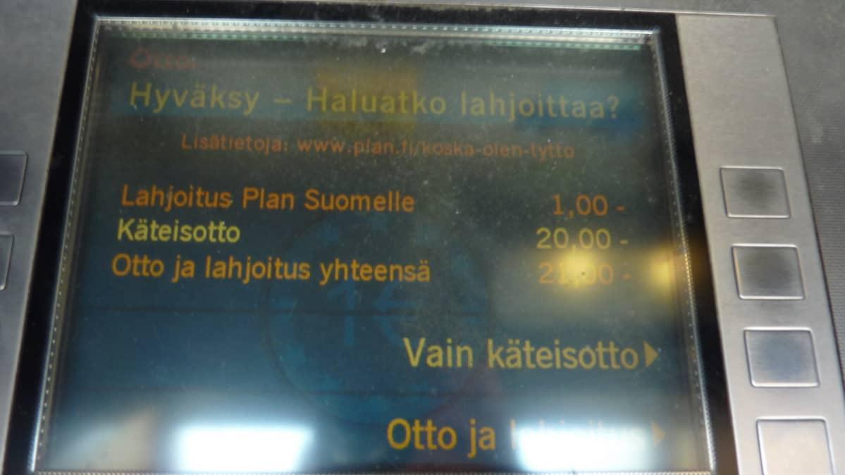 Otto-automaatin näyttö, joka kysyy lahjoitusta.
