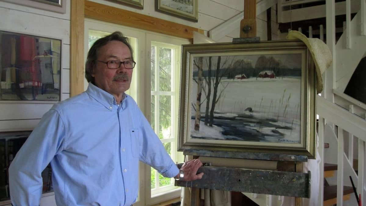 Pentti Kokko ateljeessaan maalaustensa edessä