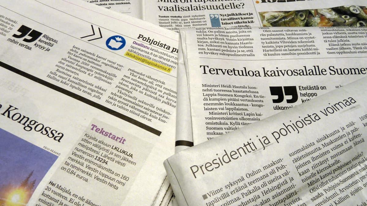 Sanomalehtiä pöydällä.