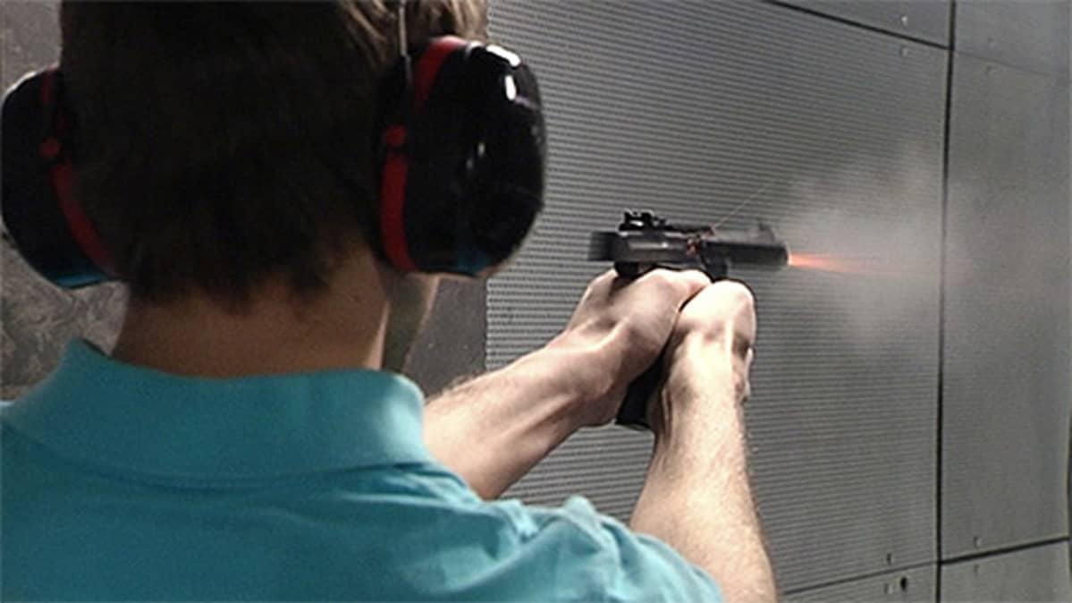 Mies ampuu pistoolilla ampumaradalla.