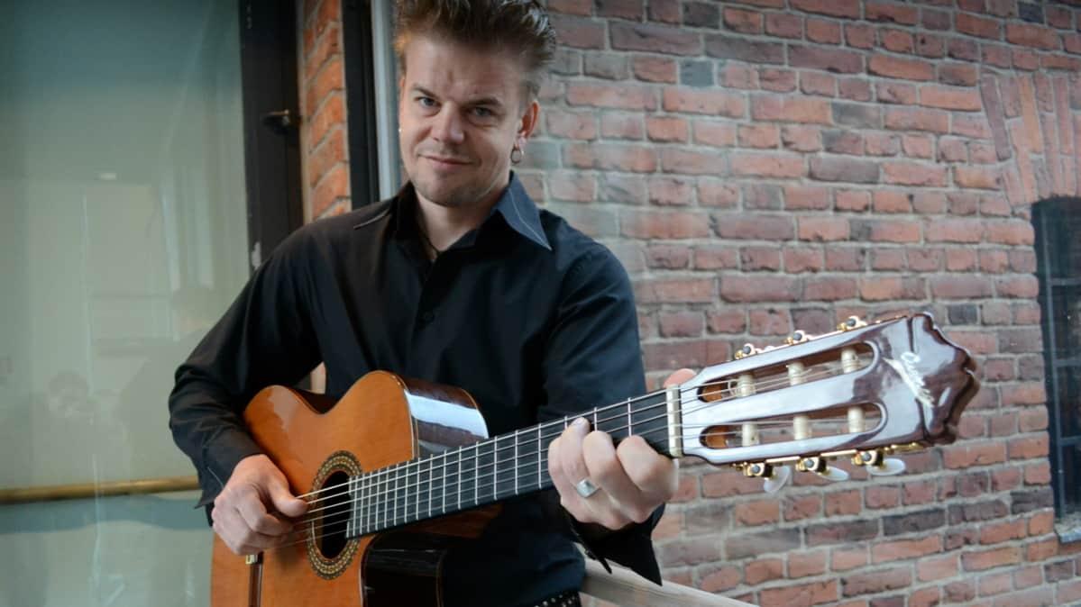 Muusikko Ilkka Esselström akustisen kitaran kanssa