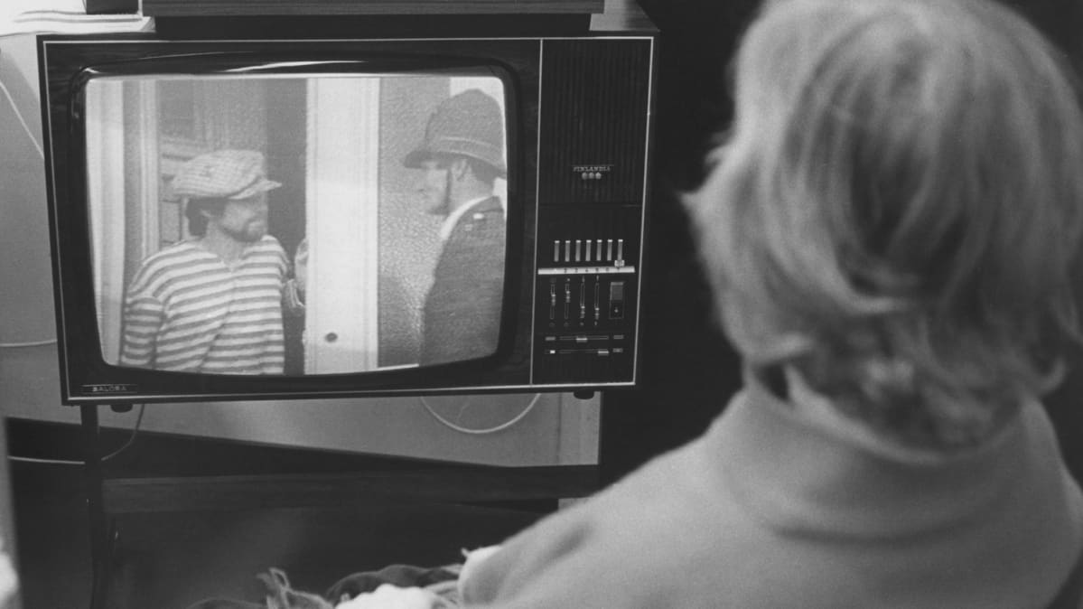 Nainen kastoo televisiota (selin).