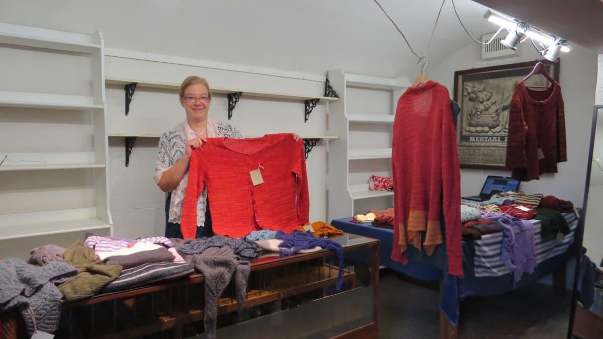 Ida Savolainen esittelee neulepaitaa Toivolan Vanhan Pihan kellarissa.