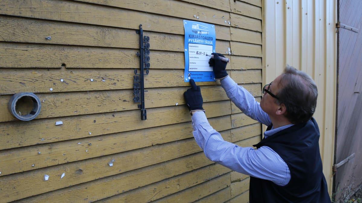kirjastoauton kuljettaja kirjoittaa tallin seinässä olevaan ilmoitukseen kirjastoauton pysähtymisajan