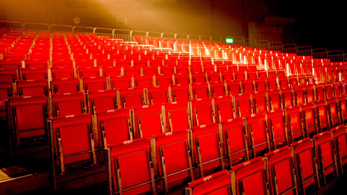 Tyhjä katsomo, punaisia tuoleja.