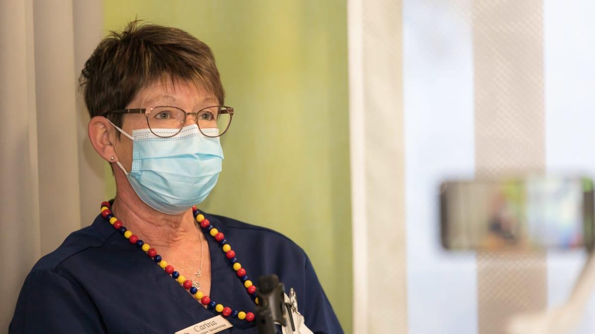 Sairaanhoitaja Carola Hanhisuanto istuu Malmin sairaalan aulassassa