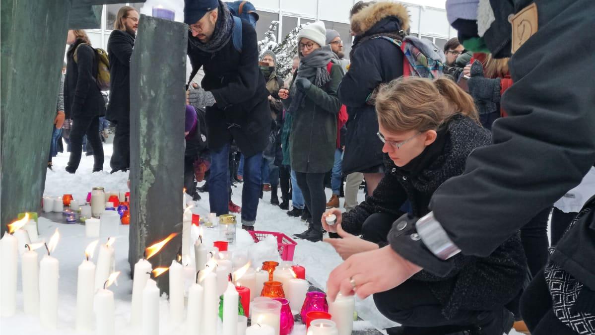 Ihmiset asettavat kynttilöitä patsaan juurelle