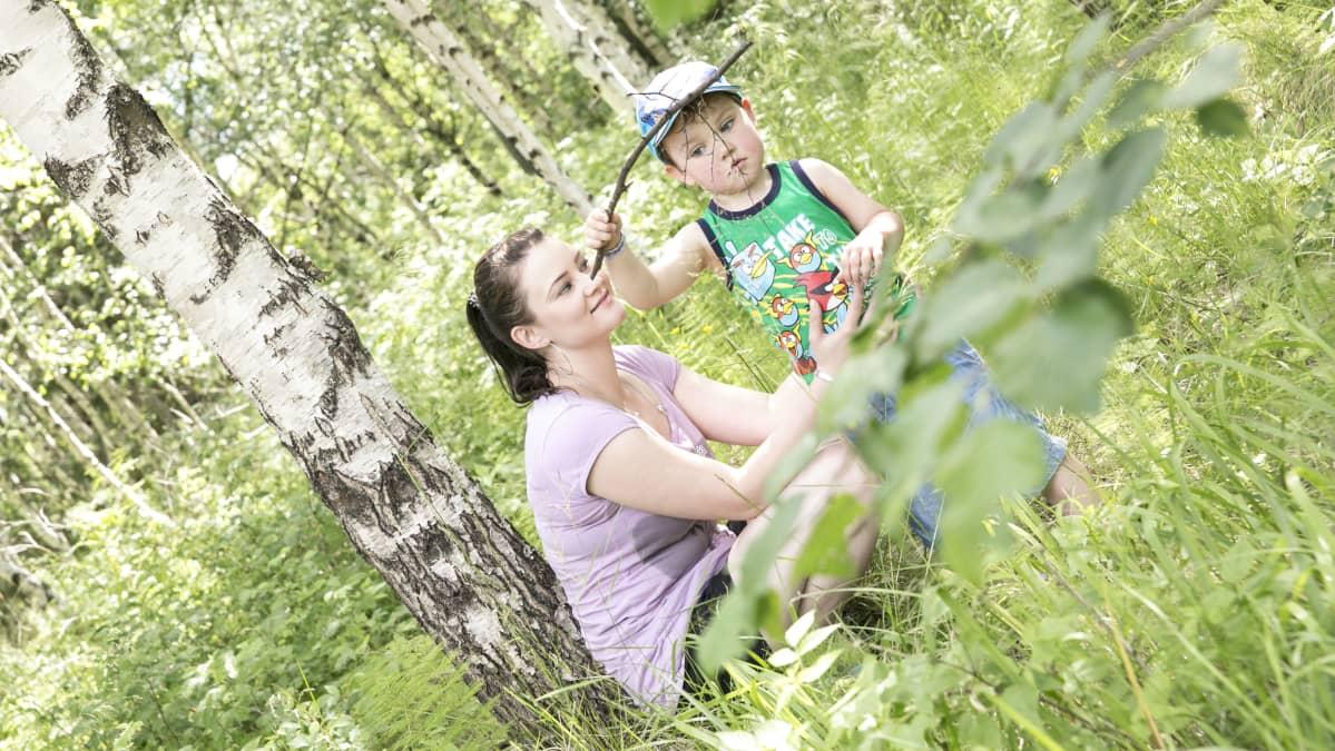 Hanna Pahlsten ja lapsi ihmettelevät oksaa kesäisessä metsässä